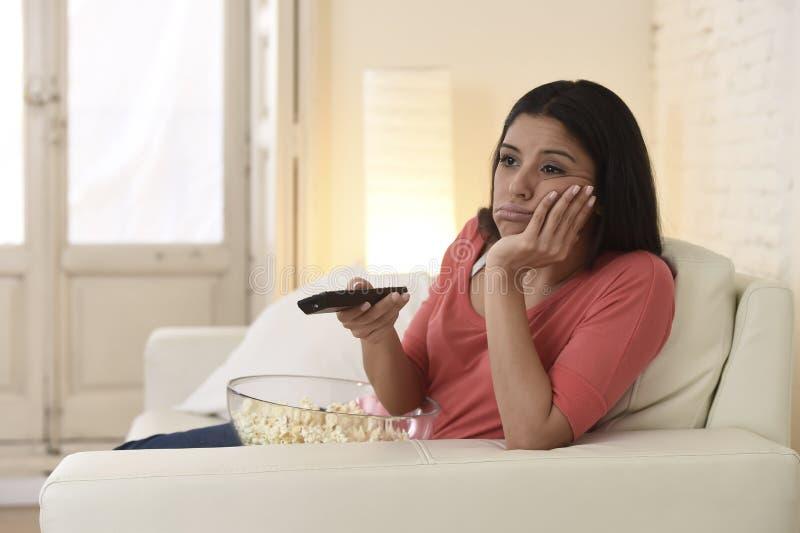 Jonge mooie vrouw die thuis vermoeid en bored op televisie letten stock afbeelding