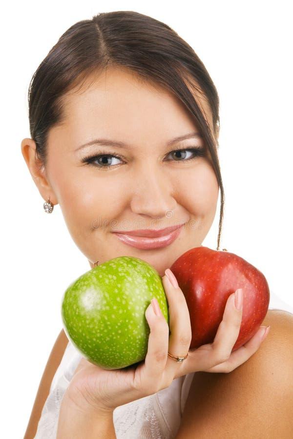Jonge mooie vrouw die twee appelen houdt stock foto's