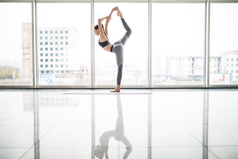 Jonge mooie vrouw die uitrekkende oefening op yogamat doen Fitness, sport, opleiding en levensstijl concept stock foto