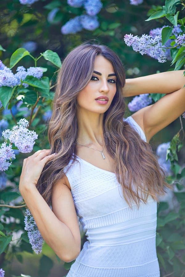 Jonge mooie vrouw die van de geur van bloeiende sering op een zonnige dag genieten royalty-vrije stock foto