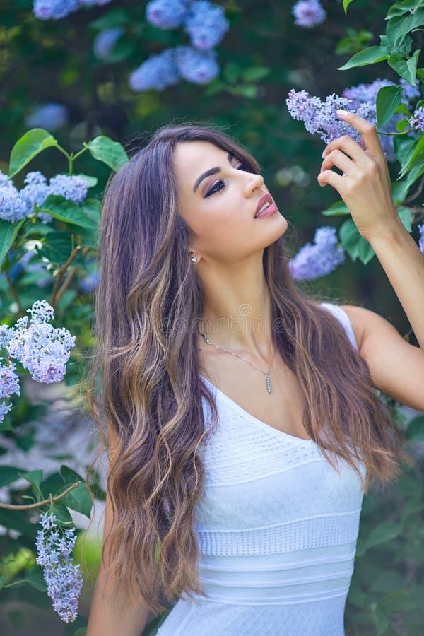Jonge mooie vrouw die van de geur van bloeiende sering op een zonnige dag genieten royalty-vrije stock afbeeldingen