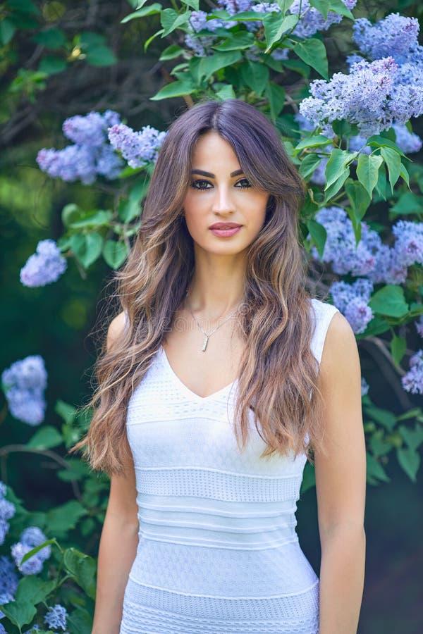 Jonge mooie vrouw die van de geur van bloeiende sering op een zonnige dag genieten royalty-vrije stock afbeelding