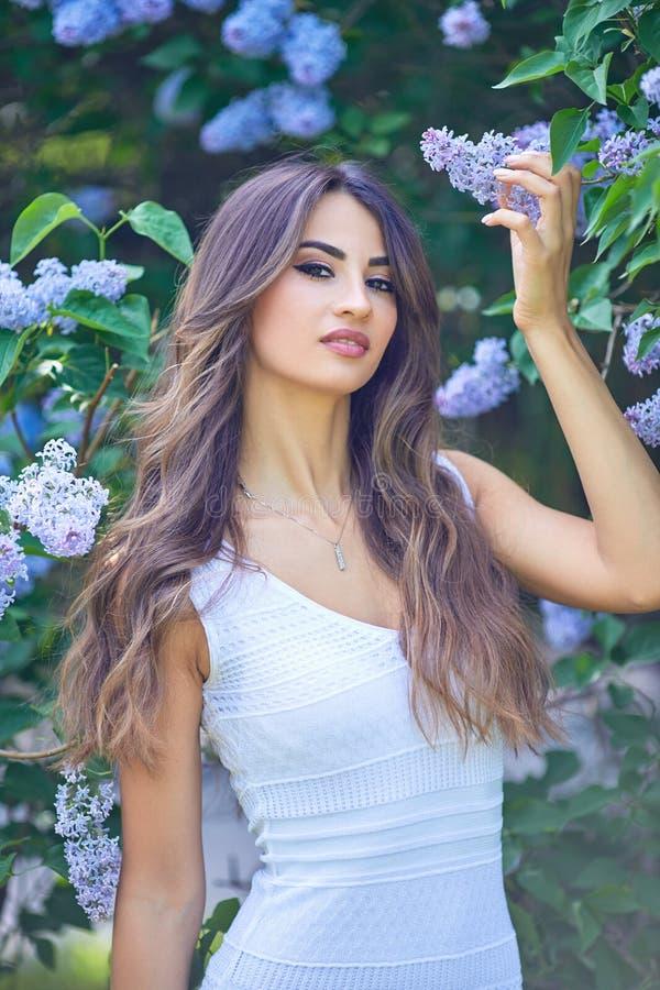 Jonge mooie vrouw die van de geur van bloeiende sering op een zonnige dag genieten stock foto
