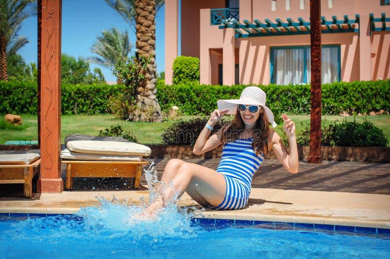 Jonge mooie vrouw die van de zon genieten en op rand van de pool zitten royalty-vrije stock afbeeldingen