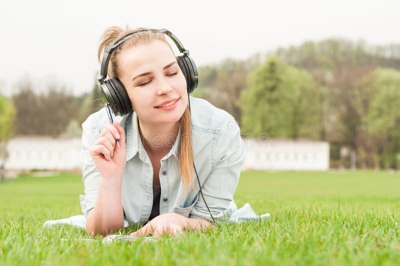 Jonge mooie vrouw die van muziek in openlucht op hoofdtelefoons genieten royalty-vrije stock fotografie