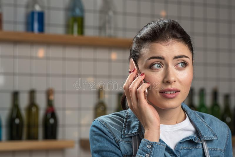 Jonge mooie vrouw die verrast terwijl het spreken op de telefoon kijken royalty-vrije stock fotografie