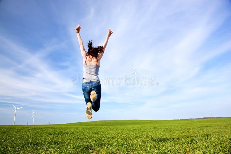 Jonge mooie vrouw die voor vreugde springen stock foto's