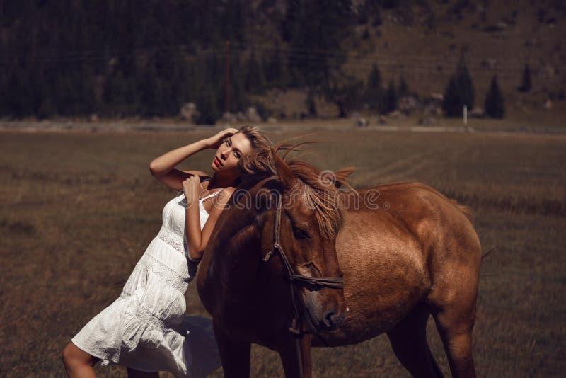 Jonge mooie vrouw die in witte kleding met paard lopen stock foto's