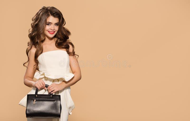 Jonge mooie vrouw die in witte kleding zwarte handtas houden royalty-vrije stock foto