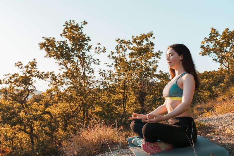 Jonge mooie vrouw die yoga doen en in het Park mediteren Het concept yoga, sporten en meditatie stock afbeeldingen