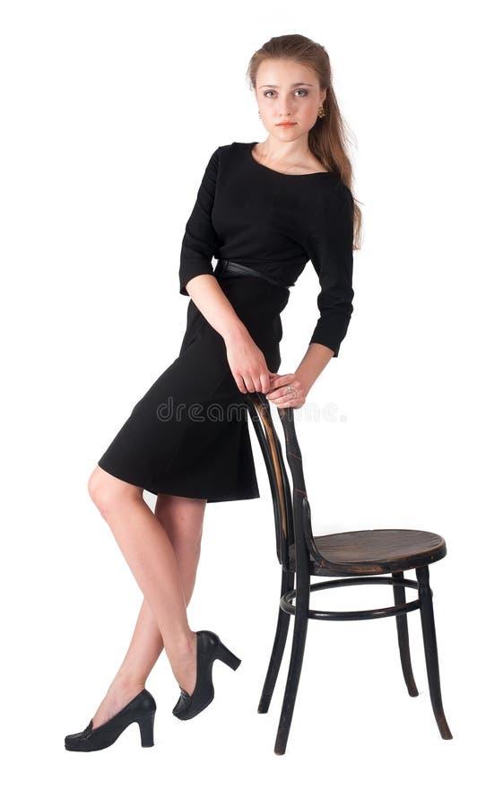 Aantrekkelijke donkerbruine vrouwenholding op stoel royalty-vrije stock foto's