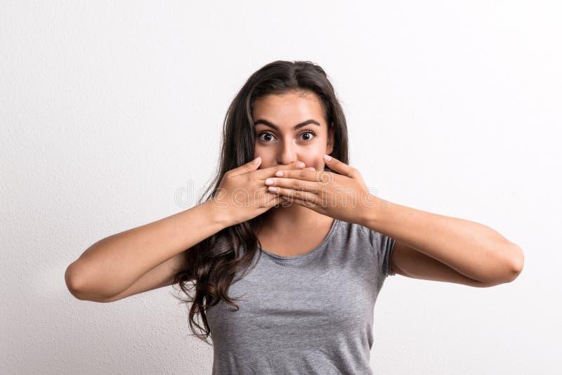 Jonge mooie vrouw die zich in een studio in studio bevinden, die mond behandelen met handen stock foto