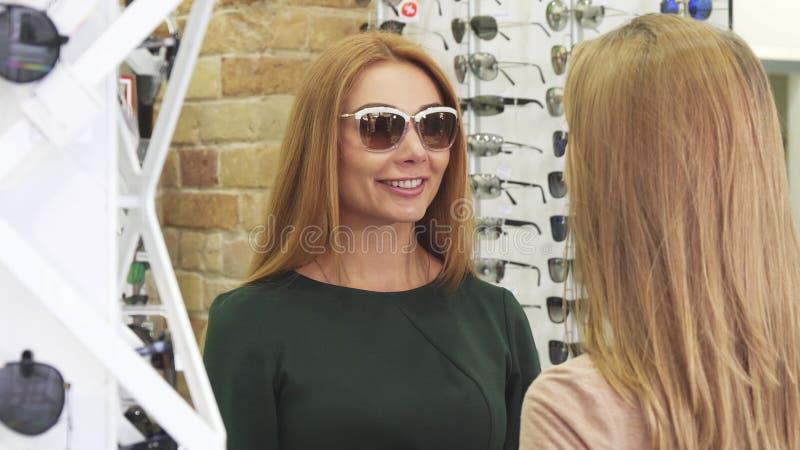 Jonge mooie vrouw die zonnebril proberen die met haar vriend winkelen stock foto's