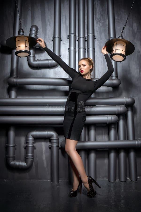 Jonge, mooie vrouw die in zwarte kleding twee retro lampen houden royalty-vrije stock foto