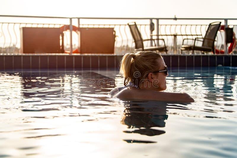 Jonge mooie Vrouw die in zwembad bij het luxueuze kijken op zonneschermparasol zonnebaden in Egypte Luxor stock fotografie
