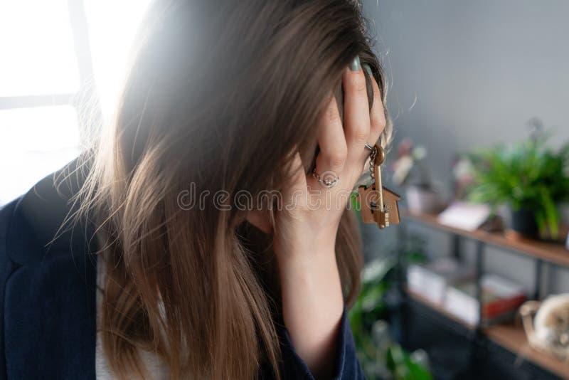 Jonge mooie vrouw duwt zijn hand tegen zijn hoofd De vertraging bij een hypotheeklening Verlies van onroerend goed op stock foto