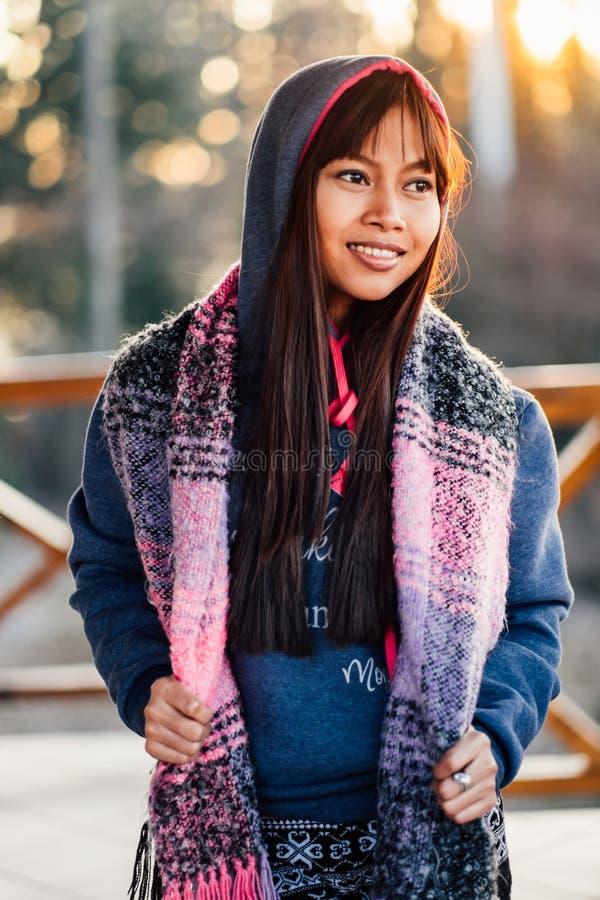 Jonge mooie vrouw in een blauwe sweater met kleurrijke sjaal tijdens koud weer buiten het balkon stock afbeeldingen
