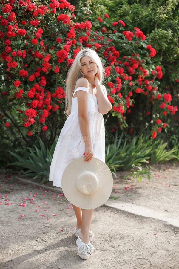 Jonge mooie vrouw in een hoed, dichtbij een grote struik van rode rozen in de de lentetuin in openlucht royalty-vrije stock fotografie