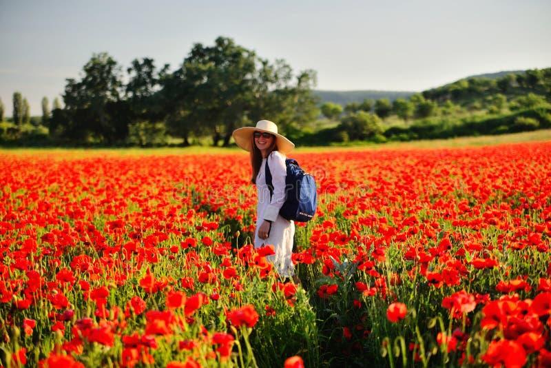 Jonge mooie vrouw in een hoed in een het bloeien ervaring van het papavergebied royalty-vrije stock foto's