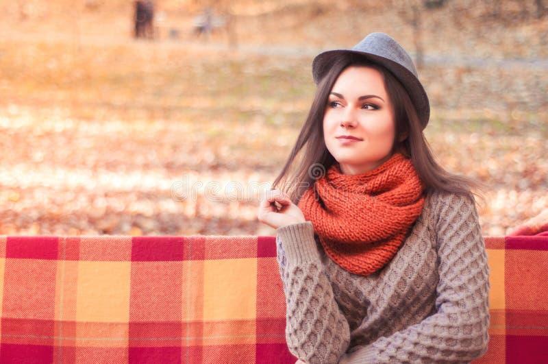 Jonge mooie vrouw in een hoedenzitting op een bank in een de herfstpark royalty-vrije stock fotografie