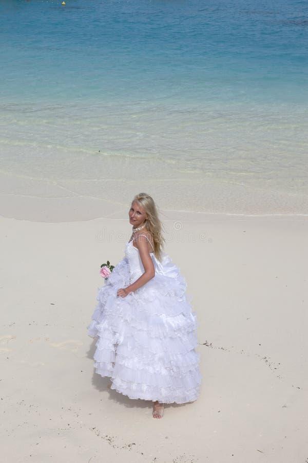 Jonge mooie vrouw in een lange witte bruidkleding op het zand op het strand door het blauwe overzees royalty-vrije stock afbeelding