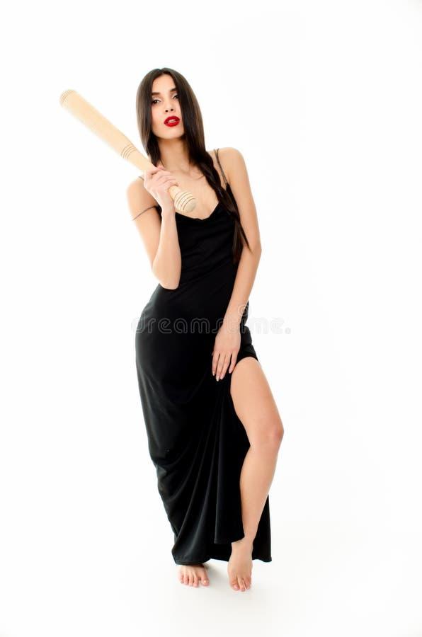 Jonge mooie vrouw in een zwarte kleding met een honkbalknuppel op een witte achtergrond stock afbeeldingen