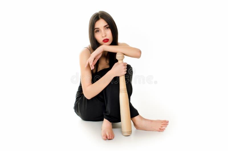 Jonge mooie vrouw in een zwarte kledingszitting met een honkbalknuppel op een witte achtergrond stock afbeelding