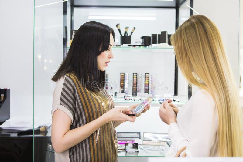 Jonge mooie vrouw en schoonheidsadviseur in winkel stock afbeelding