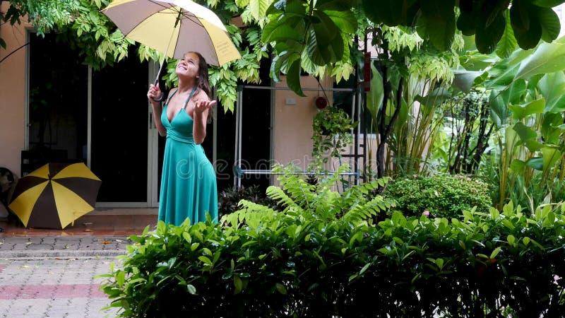Jonge mooie vrouw in groene kledingsgangen in de regen Hand van vrouwen die een paraplu houden royalty-vrije stock afbeeldingen