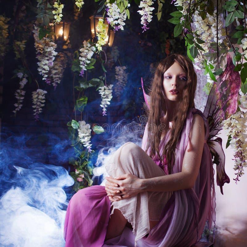 Jonge mooie vrouw in het beeld van feeën, magisch donker bos royalty-vrije stock fotografie