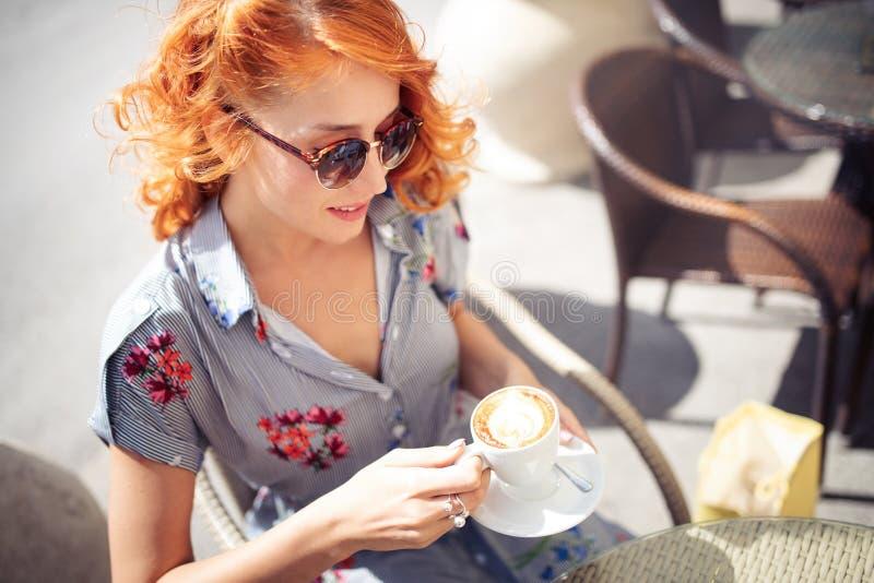 Jonge mooie vrouw het drinken cappuccino, koffie in koffie in openlucht stock fotografie
