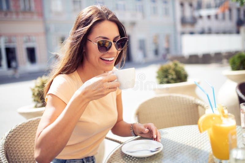 Jonge mooie vrouw het drinken cappuccino, koffie in koffie in openlucht stock afbeeldingen