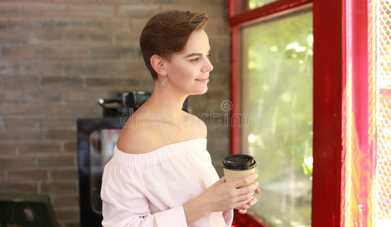 Jonge mooie vrouw het drinken koffie in bureau, naast het glasvenster royalty-vrije stock afbeeldingen