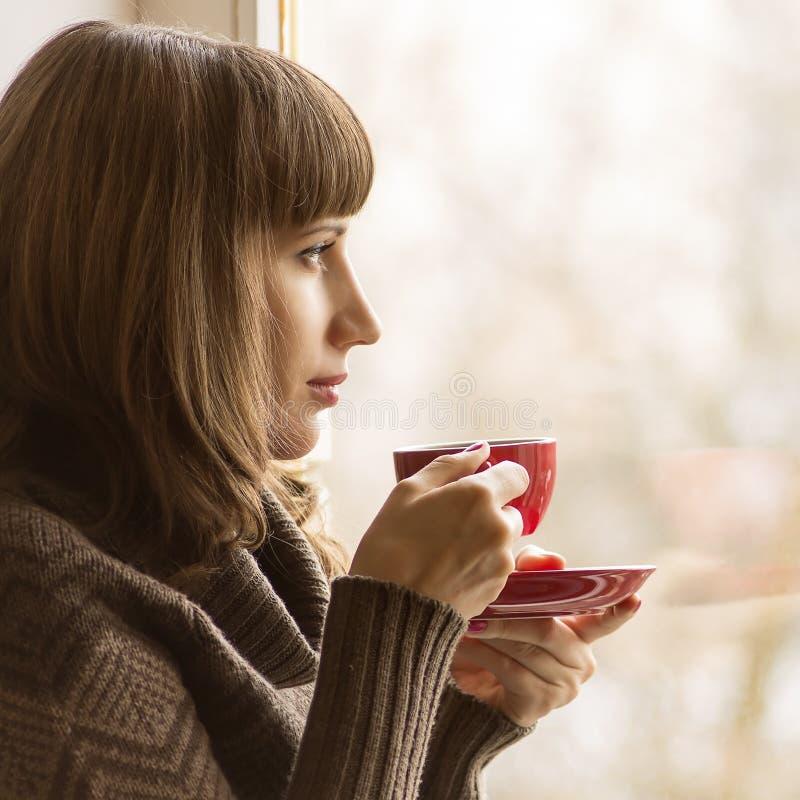 Jonge Mooie Vrouw het Drinken Koffie dichtbij Venster in Koffie stock afbeeldingen