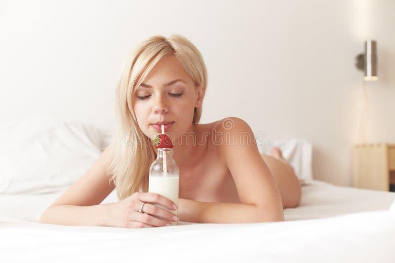 Jonge mooie vrouw het drinken melk royalty-vrije stock afbeeldingen