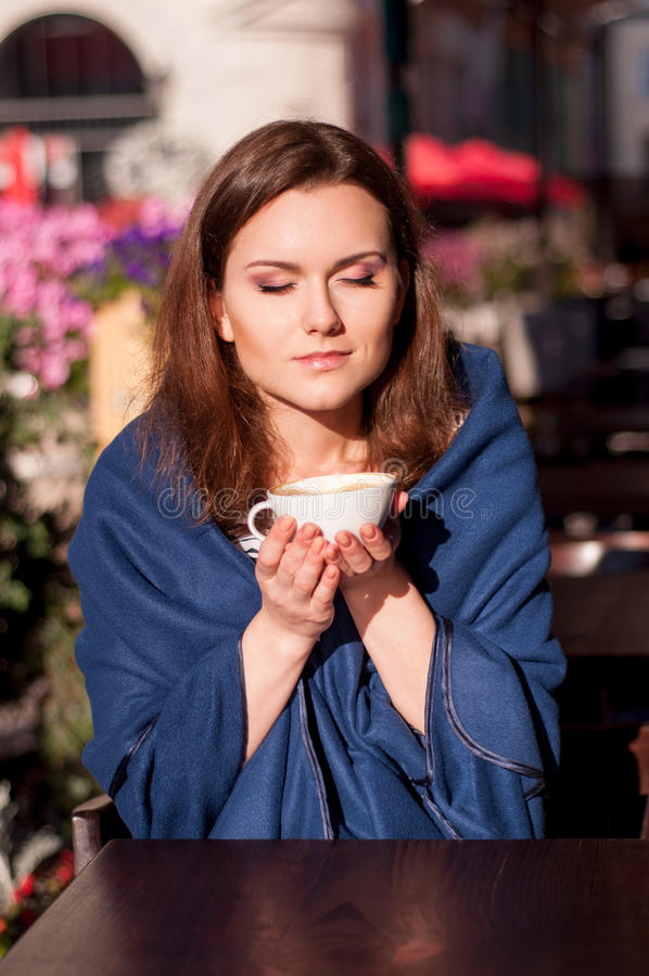 Jonge mooie vrouw het drinken ochtendkoffie in een openluchtkoffie stock fotografie