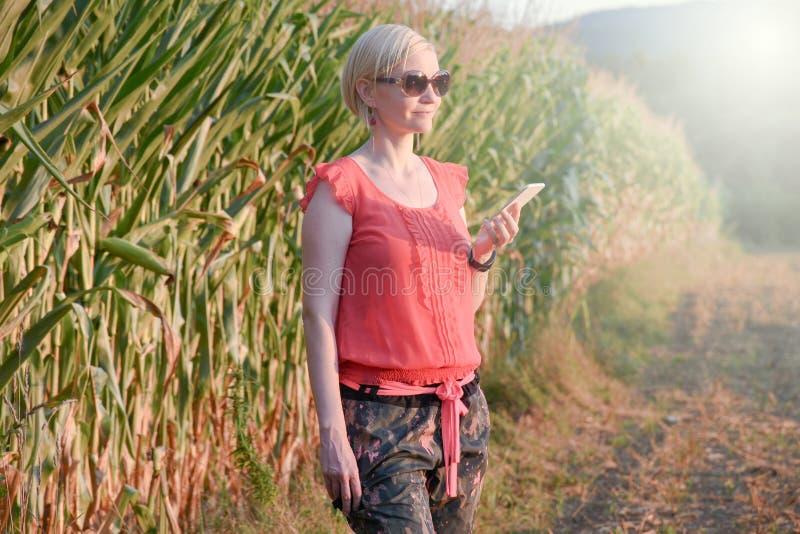 Jonge mooie vrouw in het kleurrijke doeken en zonnebril openlucht spreken op de celtelefoon stock afbeeldingen