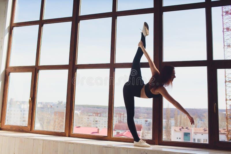 Jonge mooie vrouw het praktizeren yoga en gymnastiek- Wellnessconcept Klassen in enige sporten royalty-vrije stock afbeelding