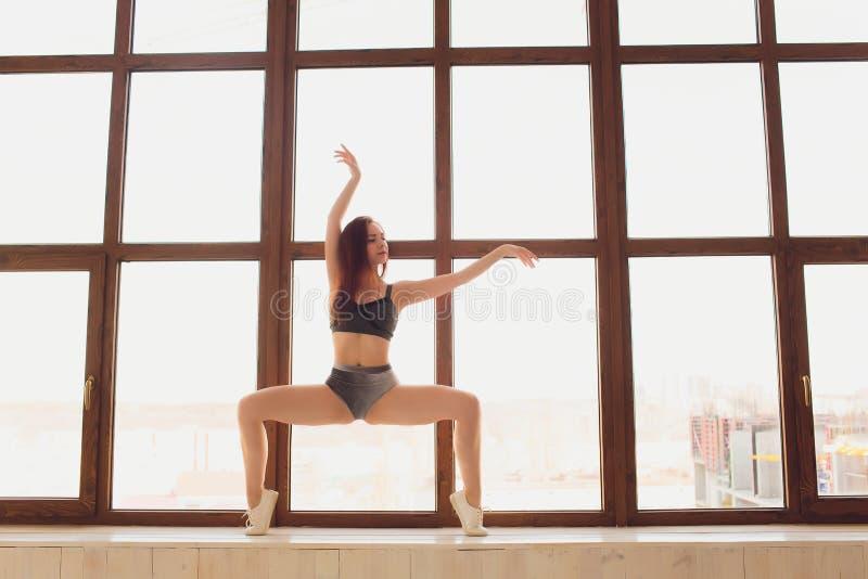 Jonge mooie vrouw het praktizeren yoga en gymnastiek- Wellnessconcept Klassen in enige sporten royalty-vrije stock foto's