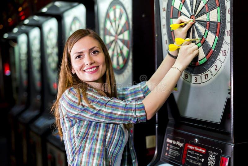 Jonge mooie vrouw het spelen pijltjes in een club royalty-vrije stock foto