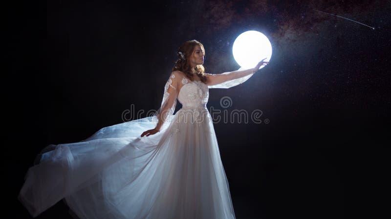 Jonge mooie vrouw in huwelijkskleding met brede lichte rok Donkere achtergrond, fantasiestijl stock afbeeldingen