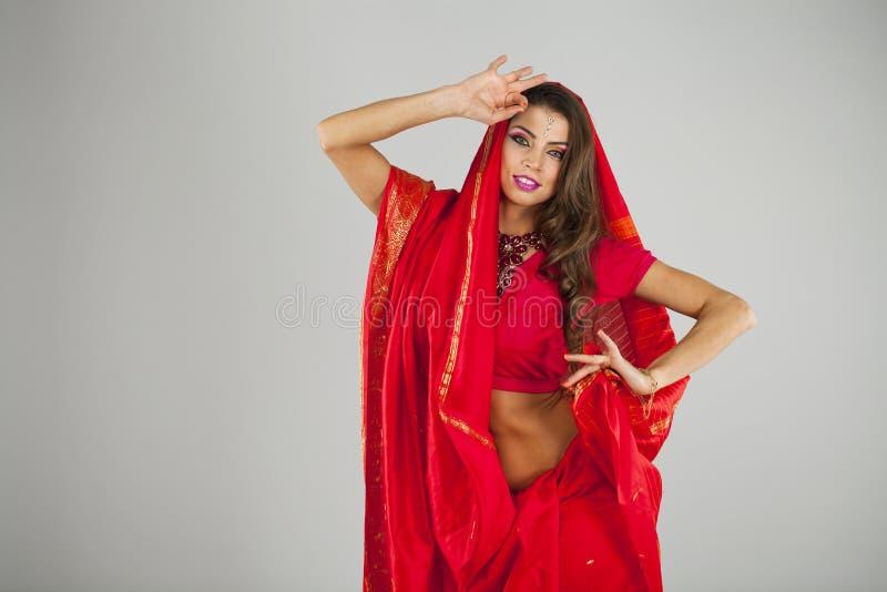 Jonge mooie vrouw in Indische rode kleding stock foto's