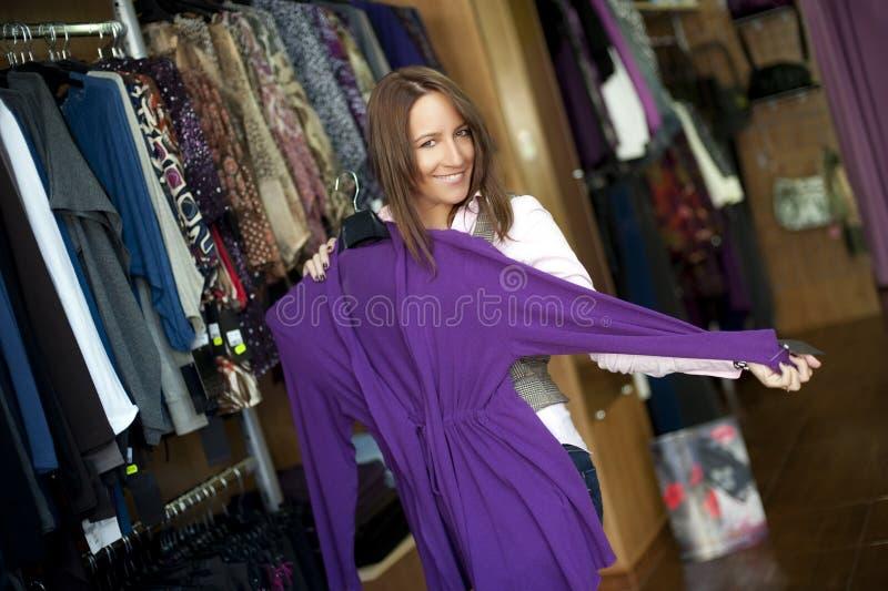Jonge mooie vrouw in klerenopslag. stock fotografie