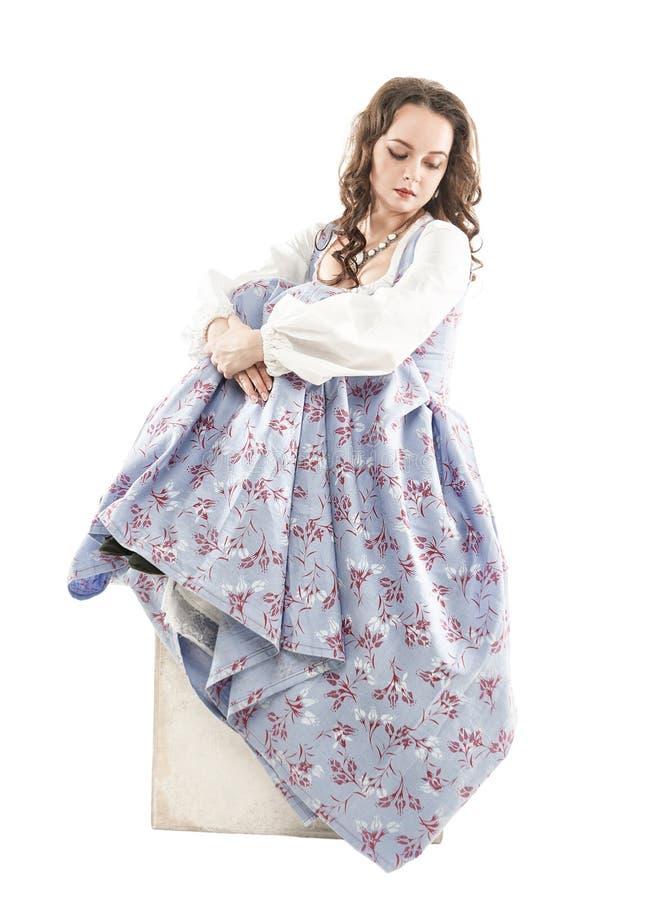 Jonge mooie vrouw in lange middeleeuwse geïsoleerde kledingszitting stock afbeeldingen