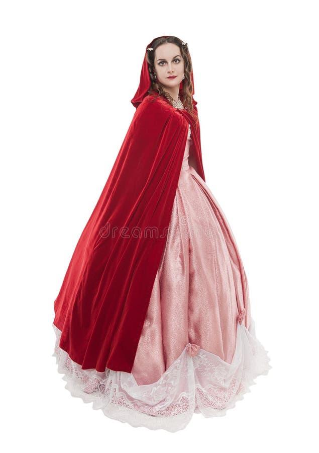 Jonge mooie vrouw in lange middeleeuwse ge?soleerde kleding en rode mantel stock fotografie