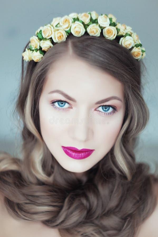 Jonge mooie vrouw met bloemen in haar en blauwe ogen royalty-vrije stock afbeeldingen