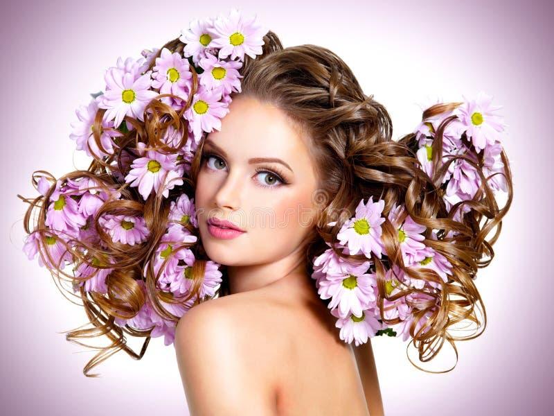 Jonge mooie vrouw met bloemen in haren stock foto's