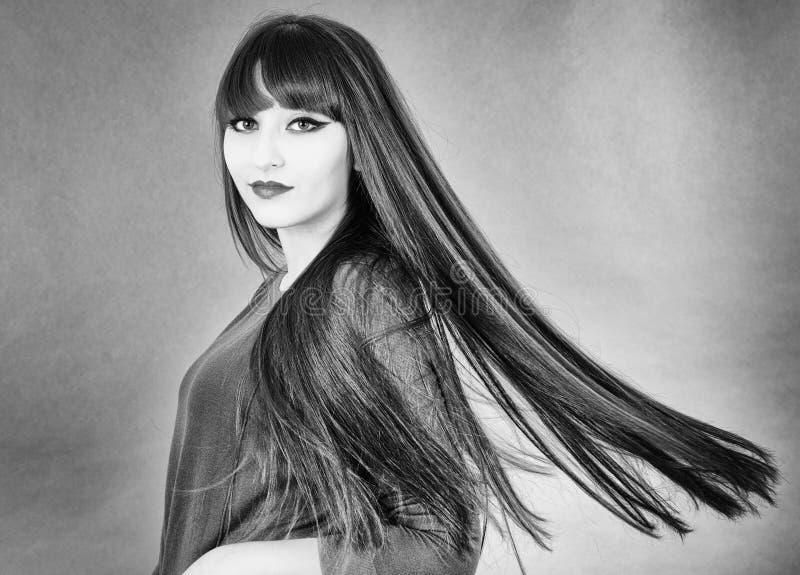 Jonge mooie vrouw met buitengewoon lang glanzend haar stock fotografie