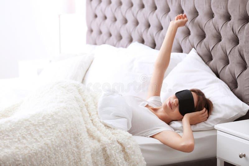 Jonge mooie vrouw met de ontwaken van het slaapmasker royalty-vrije stock foto