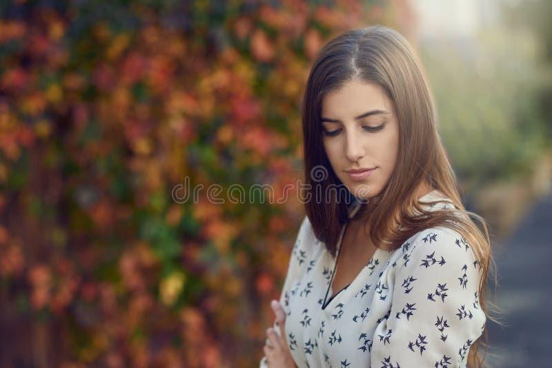 Jonge mooie vrouw met donkerbruin haar en in witte blouse stock afbeelding